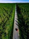 Εναέρια άποψη μιας εθνικής οδού με το κόκκινο αυτοκίνητο στη μέση του πράσινου θερινού δάσους στοκ εικόνες