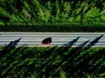 Εναέρια άποψη μιας εθνικής οδού με το κόκκινο αυτοκίνητο στη μέση του πράσινου θερινού δάσους στοκ φωτογραφία με δικαίωμα ελεύθερης χρήσης