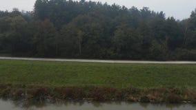 Εναέρια άποψη μιας κενής πορείας κατά μήκος ενός χλοώδους λόφου πέρα από μια λίμνη με τα δέντρα φθινοπώρου απόθεμα βίντεο