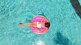 Εναέρια άποψη μιας νέας γυναίκας brunette που κολυμπά διογκώσιμο μεγάλο doughnut με ένα lap-top σε μια διαφανή τυρκουάζ λίμνη στοκ εικόνες