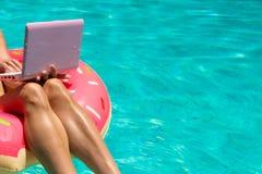 Εναέρια άποψη μιας νέας γυναίκας brunette που κολυμπά διογκώσιμο μεγάλο doughnut με ένα lap-top σε μια διαφανή τυρκουάζ λίμνη στοκ εικόνα