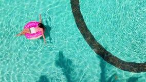 Εναέρια άποψη μιας νέας γυναίκας brunette που κολυμπά διογκώσιμο μεγάλο doughnut με ένα lap-top σε μια διαφανή τυρκουάζ λίμνη απόθεμα βίντεο
