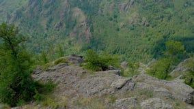 Εναέρια άποψη, μύγα κηφήνων πέρα από το καθισμένο κορίτσι σε ένα πρόσωπο απότομων βράχων απόθεμα βίντεο
