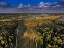 Εναέρια άποψη πέρα από ένα λιβάδι και ένα δάσος με ένα χωριό και μια λίμνη στην απόσταση Στοκ εικόνα με δικαίωμα ελεύθερης χρήσης