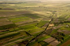 Εναέρια άποψη πέρα από μια όμορφη αγροτική σκηνή με τους πράσινους τομείς και τα δέντρα στη χρυσή ώρα την άνοιξη Στοκ Φωτογραφία