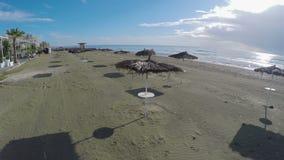 Εναέρια άποψη πέρα από την αμμώδη παραλία με το άχυρο parasols στη Λάρνακα, παραθεριστική πόλη απόθεμα βίντεο