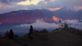 Εναέρια άποψη πέρα από Jamnik, τη Σλοβενία και την εκκλησία ST Primoz όρη ιουλιανά φιλμ μικρού μήκους