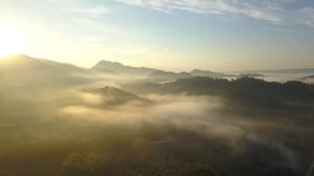 Εναέρια άποψη, πετώντας πέρα από τα βουνά και τα δέντρα με τα όμορφα σύννεφα και τον ουρανό στην ανατολή απόθεμα βίντεο