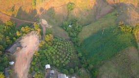 Εναέρια άποψη, πετώντας πέρα από τα βουνά και το αγρόκτημα με τα όμορφα σύννεφα και τον ουρανό στην ανατολή φιλμ μικρού μήκους