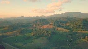 Εναέρια άποψη, πετώντας πέρα από τα βουνά και το δάσος με τα όμορφα σύννεφα και τον ουρανό στην ανατολή απόθεμα βίντεο