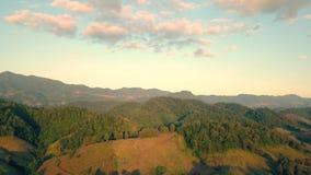 Εναέρια άποψη, πετώντας πέρα από τα βουνά και το δάσος με τα όμορφα σύννεφα και τον ουρανό στην ανατολή, απόθεμα βίντεο