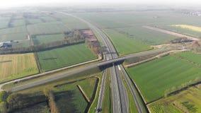 Εναέρια άποψη που πετά κοντά στην εθνική οδό που συνδέει τις μεγάλες πόλεις της Ολλανδίας Μετακίνηση των αυτοκινήτων στο autobahn φιλμ μικρού μήκους