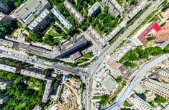 Εναέρια άποψη πόλεων με τα σταυροδρόμια και τους δρόμους, τα σπίτια, τα κτήρια, τα πάρκα και τους χώρους στάθμευσης Ηλιόλουστη θε Στοκ Εικόνα