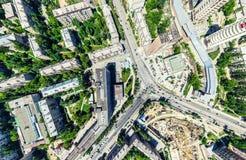 Εναέρια άποψη πόλεων με τα σταυροδρόμια και τους δρόμους, τα σπίτια, τα κτήρια, τα πάρκα και τους χώρους στάθμευσης Ηλιόλουστη θε Στοκ Φωτογραφία