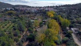 Εναέρια άποψη στο ταξίδι ενός τοπίου με ένα χωριό στο υπόβαθρο το φθινόπωρο με τον ποταμό και τα κίτρινα, πορτοκαλιά και πράσινα  απόθεμα βίντεο