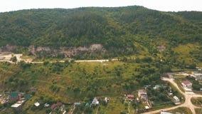 Εναέρια άποψη σχετικά με ένα μικρό χωριό στους λόφους απόθεμα βίντεο