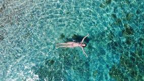 Εναέρια άποψη σχετικά με να επιπλεύσει γυναικών στη σαφή επιφάνεια θάλασσας απόθεμα βίντεο