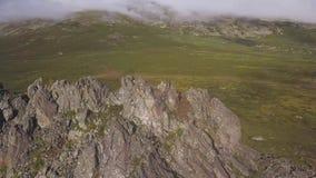 Εναέρια άποψη σχετικά με το πράσινο λιβάδι με το μόνο βράχο και το νεφελώδες υπόβαθρο ουρανού Καταπληκτικό τοπίο βουνών με το μεγ φιλμ μικρού μήκους
