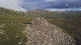 Εναέρια άποψη σχετικά με το πράσινο λιβάδι με το μόνο βράχο και το νεφελώδες υπόβαθρο ουρανού Καταπληκτικό τοπίο βουνών με το μεγ στοκ εικόνα