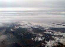 Εναέρια άποψη της γης με τα άσπρα σύννεφα που καλύπτουν τον ουρανό και το πράσινο έδαφος με τα βουνά και ορατό κάτωθι θάλασσας Στοκ Εικόνες