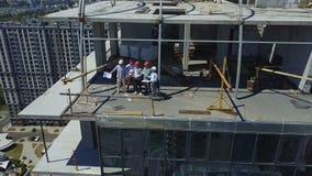 Εναέρια άποψη της επιτυχούς ομάδας των οικοδόμων, των μηχανικών και των αρχιτεκτόνων στο εργοτάξιο οικοδομής, εργαζόμενοι στη συν φιλμ μικρού μήκους