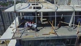 Εναέρια άποψη της επιτυχούς ομάδας των οικοδόμων, των μηχανικών και των αρχιτεκτόνων στο εργοτάξιο οικοδομής, εργαζόμενοι στη συν απόθεμα βίντεο