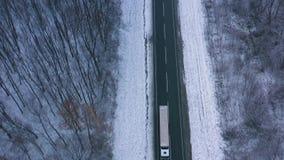 Εναέρια άποψη της κυκλοφορίας στο δρόμο που περνά μέσω του χειμερινού δάσους στον αυστηρό καιρό απόθεμα βίντεο