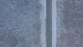 Εναέρια άποψη της κυκλοφορίας στο δρόμο που περνά μέσω του χειμερινού δάσους στον αυστηρό καιρό φιλμ μικρού μήκους