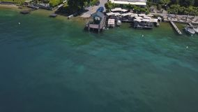 Εναέρια άποψη της μικρής αποβάθρας, του καφέ, των γιοτ και των σύγχρονων εξοχικών σπιτιών κοντά στη θάλασσα σε μια από τις νότιες απόθεμα βίντεο