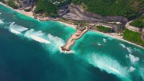 Εναέρια άποψη της παραλίας με τα τυρκουάζ ωκεάνια κύματα, δρόμος, βίλες στον απότομο βράχο σε πράσινο απόθεμα βίντεο