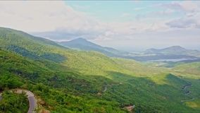 Εναέρια άποψη της πράσινης κοιλάδας ορεινών περιοχών με την καμπύλη στο δρόμο φιλμ μικρού μήκους