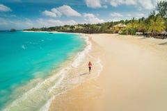 Εναέρια άποψη της τρέχοντας νέας γυναίκας στην άσπρη αμμώδη παραλία στοκ φωτογραφίες