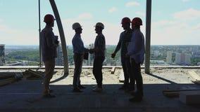 Εναέρια άποψη της χειραψίας ομάδων οικοδόμων με τον εργοδότη επιχειρησιακών ατόμων στο εργοτάξιο οικοδομής, συνάντηση της ομάδας  απόθεμα βίντεο