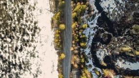 Εναέρια άποψη του αγροτικού δρόμου άνοιξη στο κίτρινο δάσος πεύκων με τη λειώνοντας λίμνη πάγου στοκ φωτογραφίες