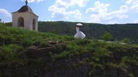 Εναέρια άποψη του γαμήλιου ζεύγους που έχει έναν περίπατο σε έναν απότομο βράχο μια ηλιόλουστη ημέρα φιλμ μικρού μήκους