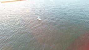Εναέρια άποψη του γιοτ που πλέει μακρυά από την ακτή σε ένα φωτεινό ηλιοβασίλεμα με τις ηλιόλουστες φλόγες και τις ακτίνες φιλμ μικρού μήκους
