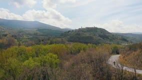 Εναέρια άποψη του δασικού δρόμου Α μεταξύ των δέντρων Και πόλη στο βουνό Ιταλία, Toskana απόθεμα βίντεο