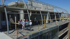 Εναέρια άποψη του εργοτάξιου οικοδομής με την ομάδα των οικοδόμων στη στέγη που συζητά το σχέδιο του προγράμματος απόθεμα βίντεο