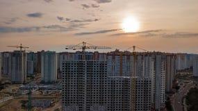 Εναέρια άποψη του εργοτάξιου οικοδομής των κτηρίων κατοικήσιμης περιοχής με τους γερανούς στο ηλιοβασίλεμα άνωθεν, αστικός ορίζον Στοκ εικόνα με δικαίωμα ελεύθερης χρήσης