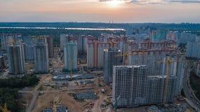 Εναέρια άποψη του εργοτάξιου οικοδομής των κτηρίων κατοικήσιμης περιοχής με τους γερανούς στο ηλιοβασίλεμα άνωθεν, αστικός ορίζον Στοκ Εικόνα