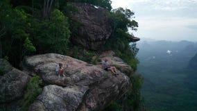 Εναέρια άποψη του ζεύγους στην άκρη του βράχου στο σημείο θέας βουνού απόθεμα βίντεο