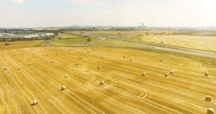 Εναέρια άποψη του καλλιεργημένου τομέα σίτου με τα δέματα του σανού στην επαρχία Άποψη της εθνικής οδού με την οδήγηση του φορτίο απόθεμα βίντεο