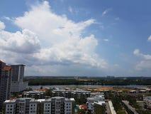 Εναέρια άποψη του μπλε ουρανού και της εικονικής παράστασης πόλης με το τεράστιο άσπρο σύννεφο Στοκ Εικόνα