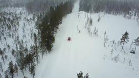 Εναέρια άποψη του μόνου κόκκινου αυτοκινήτου στο δρόμο στο όμορφο χειμερινό τοπίο του Lapland κατά τη διάρκεια χιονοπτώσεων φιλμ μικρού μήκους