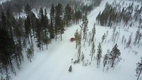 Εναέρια άποψη του μόνου κόκκινου αυτοκινήτου στο δρόμο στο όμορφο χειμερινό τοπίο του Lapland κατά τη διάρκεια χιονοπτώσεων απόθεμα βίντεο