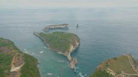 Εναέρια άποψη του νησιού, των απότομων βράχων, του μπλε νερού του ωκεανού και των κυμάτων, Μπαλί, Ινδονησία φιλμ μικρού μήκους