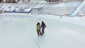 Εναέρια άποψη του πάγου που κάνει πατινάζ δύο φίλοι γυναικών υπαίθριοι, αίθουσα παγοδρομίας Medeo πάγου φιλμ μικρού μήκους