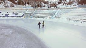 Εναέρια άποψη του πάγου που κάνει πατινάζ δύο φίλοι γυναικών υπαίθριοι, αίθουσα παγοδρομίας Medeo πάγου απόθεμα βίντεο
