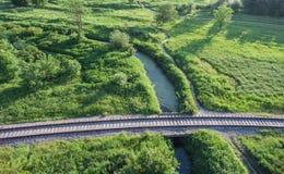 Εναέρια άποψη του του χωριού σιδηροδρόμου που πηγαίνει πέρα από τη γέφυρα Στοκ εικόνα με δικαίωμα ελεύθερης χρήσης