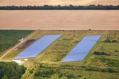 Εναέρια άποψη του φωτοβολταϊκού σταθμού παραγωγής ηλεκτρικού ρεύματος ηλιακών πλαισίων στον πράσινο τομέα στοκ εικόνες